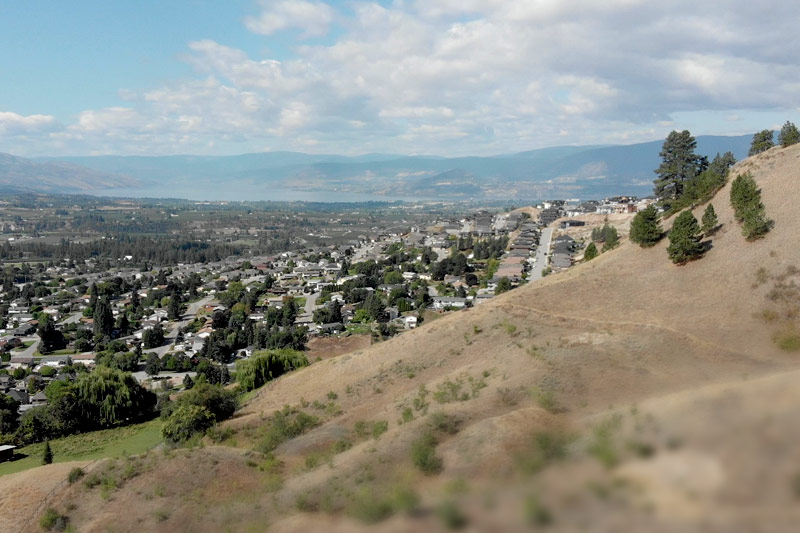View of a city from the hillside with mountains in the background