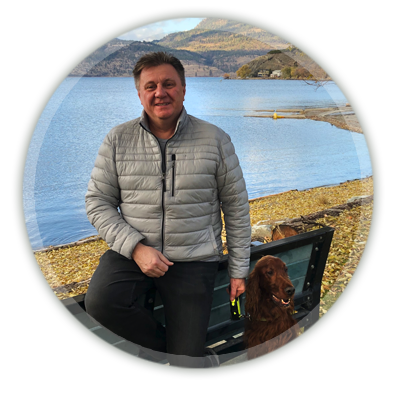 photo of a man and dog with a lake in the background